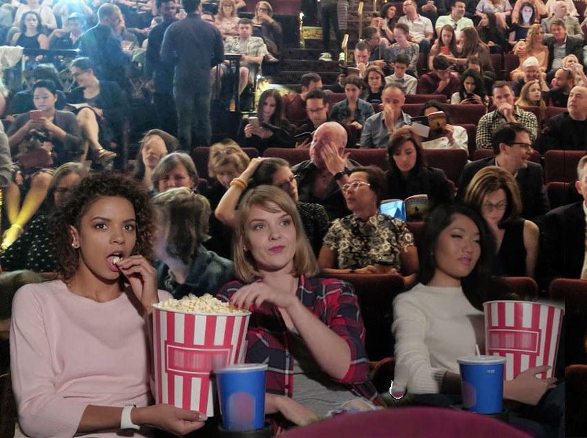 Broadway audience members eating popcorn